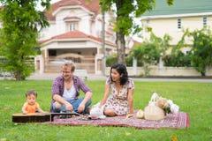 Portrait de la famille multi-ethnique heureuse collant ensemble dehors images stock