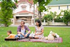 Portrait de la famille multi-ethnique heureuse collant ensemble dehors photo stock