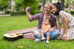 Portrait de la famille multi-ethnique heureuse prenant le selfie ensemble dehors photos libres de droits