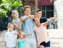 Portrait de la famille nombreuse ordinaire se tenant se dirigeante avec le doigt Photographie stock libre de droits