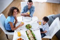 Portrait de la famille prenant le petit déjeuner ensemble Images stock