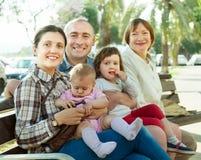 Portrait de la famille sur plusieurs générations heureuse s'asseyant sur le banc Image stock