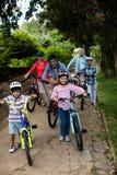 Portrait de la famille sur plusieurs générations se tenant avec la bicyclette en parc Images libres de droits