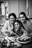 Portrait de la famille sur plusieurs générations de sourire préparant la nourriture dans la cuisine images stock