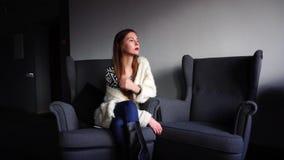 Portrait de la femelle de charme qui sourit et regarde loin, se reposant dans la chaise en café élégant l'après-midi d'hiver banque de vidéos