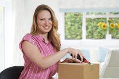 Portrait de la femme à l'aide du couteau pour ouvrir le paquet à la maison images stock