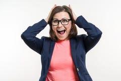 Portrait de la femme adulte étonnée très heureuse d'affaires tenant sa tête dans la stupéfaction Studio blanc de fond image libre de droits