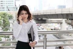 Portrait de la femme asiatique assez jeune d'affaires parlant au téléphone au fond urbain de ville photo stock