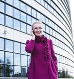 Portrait de la femme assez jeune d'affaires en verres parlant au téléphone près du bâtiment moderne, concept de personnes de mode Images libres de droits