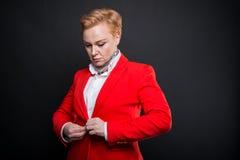 Portrait de la femme attirante d'affaires boutonnant sa veste Images stock