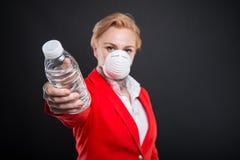 Portrait de la femme attirante d'affaires remettant le masque de port de l'eau Photos stock