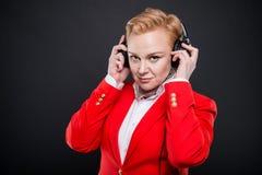 Portrait de la femme attirante d'affaires tenant des écouteurs Photographie stock
