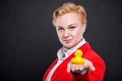 Portrait de la femme attirante d'affaires tenant le canard en caoutchouc Image libre de droits