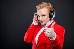Portrait de la femme attirante d'affaires tenant la représentation d'écouteurs Images stock