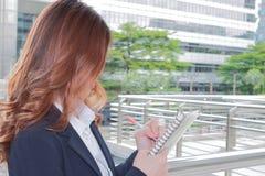Portrait de la femme attirante de secrétaire écrivant une note pour son travail au bureau extérieur photos libres de droits