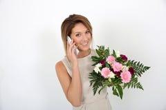 Portrait de la femme avec le bouquet de fleur parlant au téléphone Image libre de droits