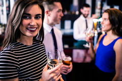 Portrait de la femme ayant une boisson avec des amis Image libre de droits