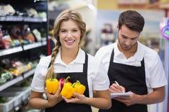 Portrait de la femme blonde de sourire ayant des légumes et écrivant sur le bloc-notes Image stock