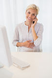 Portrait de la femme blonde de sourire employant l'ordinateur et téléphoner Photographie stock libre de droits