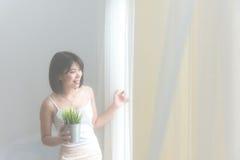 Portrait de la femme blonde et attirante se tenant à côté de la fenêtre derrière les rideaux pendant le matin, ton de vintage, Photo libre de droits
