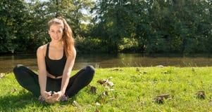 Portrait de la femme convenable de jeunes s'asseyant sur l'herbe photographie stock