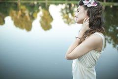 Portrait de la femme détendant par le bord de lac Images stock