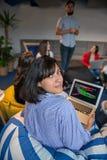 Portrait de la femme d'affaires à l'aide de l'ordinateur portable tandis que collègue vu à l'arrière-plan au bureau créatif photographie stock libre de droits