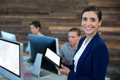 Portrait de la femme d'affaires de sourire à l'aide du comprimé numérique photos stock