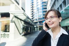 Portrait de la femme d'affaires en verres dans la ville parlant sur le téléphone et le sourire image libre de droits
