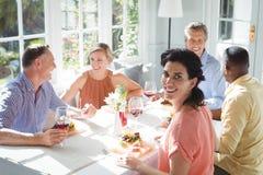 Portrait de la femme de sourire ayant le repas avec des amis Photographie stock libre de droits