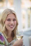 Portrait de la femme de sourire ayant le vin pendant le déjeuner Image stock
