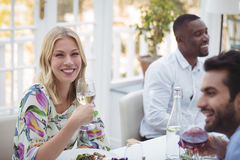 Portrait de la femme de sourire ayant le vin pendant le déjeuner Image libre de droits
