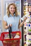 Portrait de la femme de sourire ayant sur ses mains une bouteille à lait et un panier à provisions frais Photos libres de droits