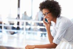 Portrait de la femme de sourire dans le bureau parlant au téléphone Image libre de droits