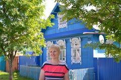 Portrait de la femme des années moyennes contre le h en bois bleu Photographie stock