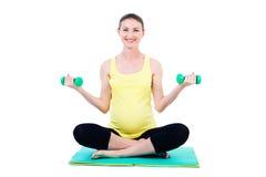 Portrait de la femme enceinte de sourire s'asseyant sur le tapis avec le dumbb Images libres de droits