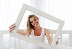 Portrait de la femme enceinte qui regarde un cadre de tableau Images stock