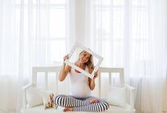 Portrait de la femme enceinte qui regarde un cadre de tableau Photographie stock