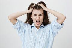Portrait de la femme européenne folle et furieuse criant et semblant aliénée tout en retirant des cheveux au-dessus de fond gris Photo libre de droits
