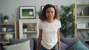 Portrait de la femme fâchée d'Afro-américain hurlant et faisant des gestes exprimant des émotions négatives se tenant en appartem banque de vidéos