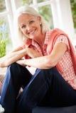 Portrait de la femme âgée par milieu s'asseyant sur le siège fenêtre Photographie stock