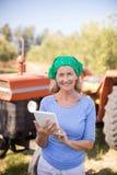 Portrait de la femme heureuse à l'aide du comprimé numérique dans la ferme olive Photographie stock