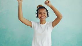 Portrait de la femme heureuse d'Afro-américain écoutant la musique par les écouteurs sans fil et dansant appréciant la mélodie clips vidéos