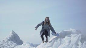 Portrait de la femme mignonne dans la veste chaude marchant sur le glacier, tenant son téléphone portable dans la main augmentée, clips vidéos