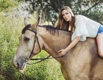 Portrait de la femme mignonne de brune montant un cheval images stock