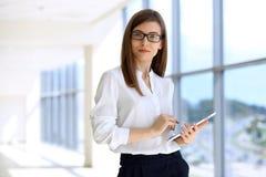 Portrait de la femme moderne d'affaires travaillant avec l'ordinateur portable dans le bureau, secteur d'espace de copie Photo stock
