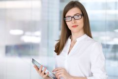 Portrait de la femme moderne d'affaires travaillant avec la tablette dans le bureau Image libre de droits