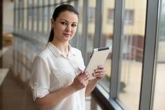 Portrait de la femme occupée d'affaires travaillant à l'ipad tout en se tenant prêt la fenêtre dans le bureau Petite entreprise B images stock