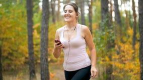 Portrait de la femme sportive de sourire jooging dans la forêt et la musique de écoute avec des écouteurs photo stock