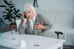 portrait de la femme supérieure avec le mal de coeur parlant sur le smartphone à la table avec des médecines image libre de droits